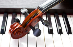 Violin and piano keyboard. Closeup part of music background royalty free stock images