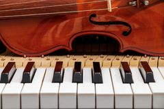 Violin on the piano keyboard royalty free stock photography
