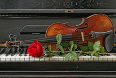 Violin piano rose. Old antique piano violin and red rose stock images