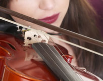 Violin play. A violin is played with a caucasian face in the background Royalty Free Stock Image