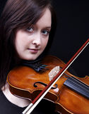 Violin play. A beautiful young orechstra musician plays the violin, set against a dark background Stock Photos