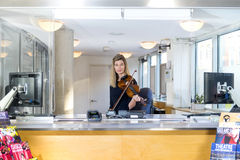 Violin player behind ticket counter royalty free stock photography