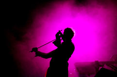 Violin player in concert. With purple background Royalty Free Stock Image