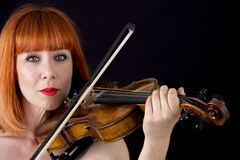Violin player holding violin, woman with red hair. Violin player woman with red hair close up isolated on black background Stock Images