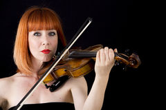 Violin player holding violin, woman with red hair Royalty Free Stock Photography