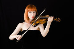 Violin player holding violin, woman with red hair. Violin player woman with red hair close up isolated on black background Stock Photo