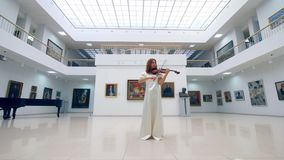 Violin player stands in a museum room alone, performing. 4K stock video