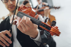 Violin players performing. Professional violinists performing, male player on foreground, blank copy space on the right Stock Image