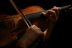 Violin playing hands. Violin is in the hands of professional violinist. Details of violin playing isolated on black background Royalty Free Stock Photo