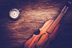 Violin and pocket watch on grunge dark wood background. Stock Photos