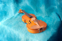 Violin resting on blue Royalty Free Stock Image