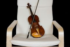 Violin resting on a chair Stock Image