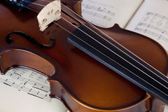Violin resting on open sheet music book Royalty Free Stock Image