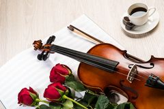 Violin, rose, coffee and music books Stock Photo