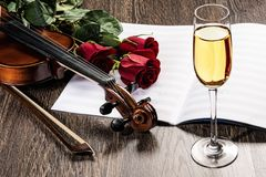 Violin, rose, glass of champagne and music books Stock Photos
