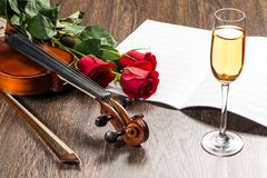 Violin, rose, glass of champagne and music books Stock Photography