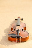 Violin on sandy beach. Music concept Royalty Free Stock Photography