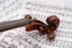 Violin scroll on sheet music Stock Images
