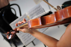 Violin and sheet music. In the foreground there's a detail of a violin played by a woman, in the background a sheet music Stock Image