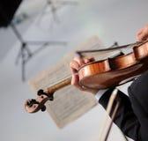 Violin and sheet music. A man playing a violin and sheet music Stock Photo