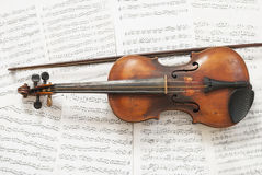 Violin and sheet music. An old violin with a bow on the background music Royalty Free Stock Photo