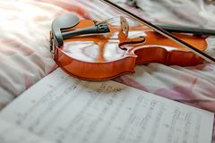 Violin and the sheet of music note on the bed. Vintage violin and the sheet of music note on the flowery bed in girly bedroom. Playing music instrument at home royalty free stock image
