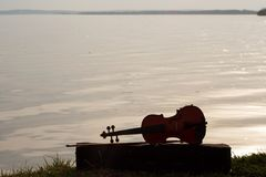 Violin of the shore of a big lake stock image