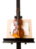 Violin standing on painting easel isolated. Old violin standing on painting easel isolated on white Stock Photo