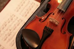 Violin and stave. Violin in open case; stave with notes lying below and blurred Royalty Free Stock Photos