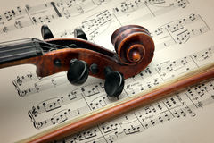 Violin stick, peg box and scroll, on music sheet Stock Photo
