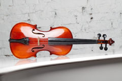 Violin on the white grand piano with brick wall background. Horizontal Stock Images