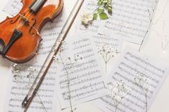 Violin and white rose on music sheets with gypsophila flowers, above vantage point photography. Violin and white rose on music sheets with gypsophila flowers stock photo