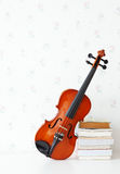 Violin on white table with old book beside Stock Images