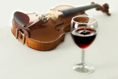 Violin an wine. Glass of red wine dropping and violin Stock Image