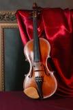 Violine auf roter Seide Stockfotos