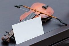 Violine miniatura en piano de madera oscuro con la tarjeta de visita en blanco Foto de archivo
