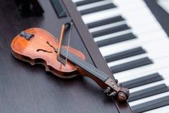 Violine miniature sur le piano en bois foncé Images stock