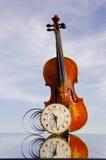 Violine mit alter Borduhr auf Spiegel Stockfoto