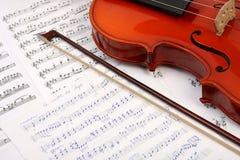 Violine mit Bogen auf Musikbuch stockfotografie