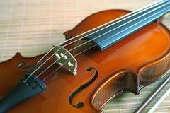 Violine mit einem Bogen, der auf einer Matte von einem Bambus liegt Stockfoto