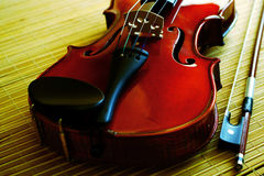 Violine mit einem Bogen, der auf einer Matte von einem Bambus liegt Lizenzfreies Stockfoto