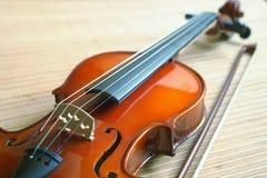 Violine mit einem Bogen, der auf einer Matte von einem Bambus liegt Stockbilder