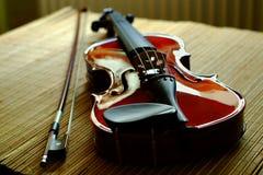 Violine mit einem Bogen, der auf einer Matte von einem Bambus liegt Stockbild