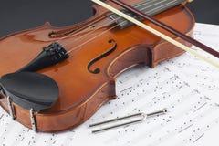 Violine und Bogen auf musikalischen Anmerkungen lizenzfreie stockfotografie