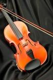 Violine und Bogen auf schwarzer Seide Stockfoto