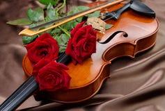 Violine und rote Rosen auf einem silk Hintergrund Abschluss oben lizenzfreie stockfotos