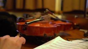 Violines en vestuario antes de la mano del concierto con el lápiz y el cuaderno almacen de video