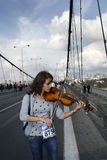 Violinist. Woman plays violin on the Bosphorus Bridge during the 27th Intercontinental Eurasia Marathon run on October 28,2007,in Istanbul,Turkey Royalty Free Stock Image