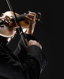 The violinist. Musician playing violin on dark background Stock Image