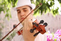 Violinist. A male violinist playing and looking at the violin Royalty Free Stock Images